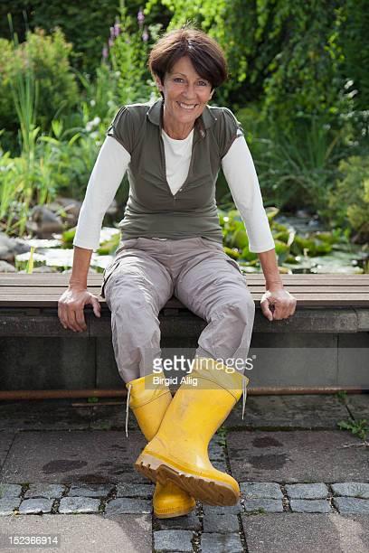 Elderly woman sitting in her garden