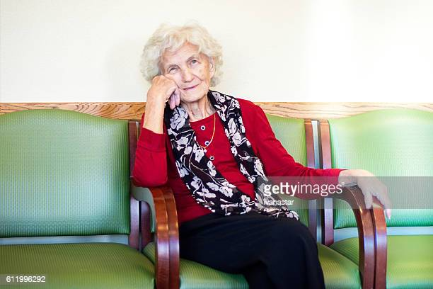 Elderly woman sitting in waiting room at doctor office