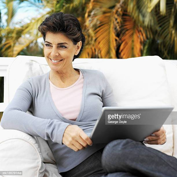 Elderly woman sitting on a couch working on a laptop