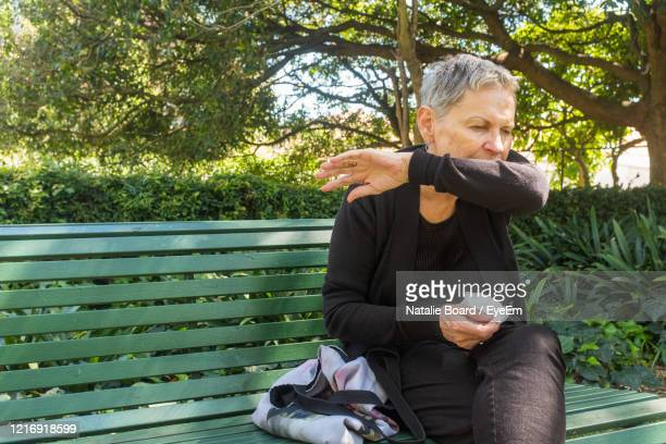 elderly woman sitting on bench outdoors coughing into elbow and holding tissue - coronavirus concept - cough stock pictures, royalty-free photos & images