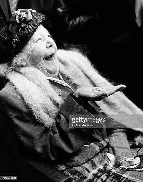 Elderly woman smiling, holding coins (B&W)
