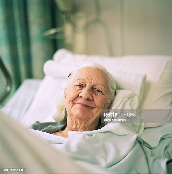 elderly woman smiling, lying in hospital bed, portrait - old woman in sick bed stock photos and pictures