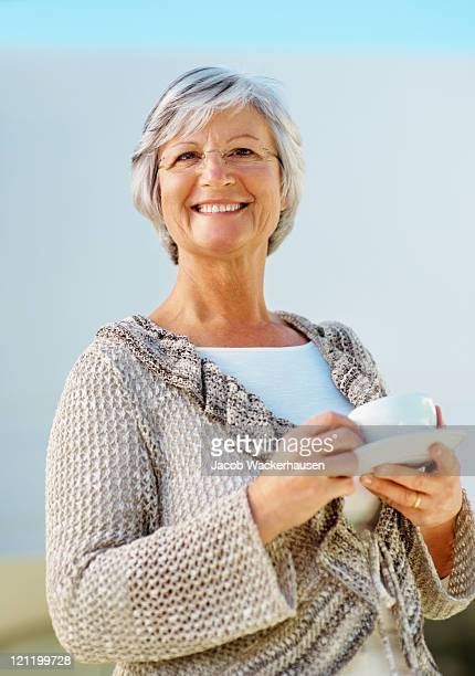 Elderly woman smiling with a cup of coffee