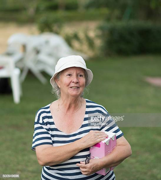 elderly woman smiling with carton of milk - milk carton stock photos and pictures