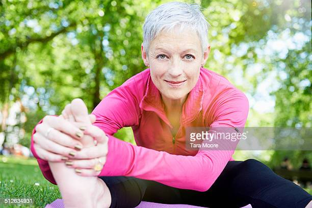 elderly woman stretching in parl - stretching stock pictures, royalty-free photos & images