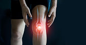 Elderly woman suffering from pain in knee. Tendon problems and Joint inflammation on dark background.