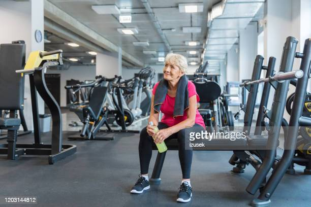 elderly woman taking a break after exercising at rehab gym - izusek stock pictures, royalty-free photos & images