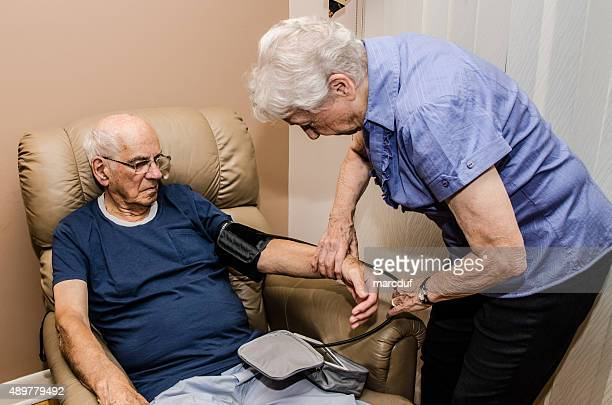 Elderly woman taking blood pressure of her husband