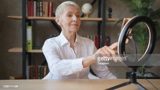 elderly woman teacher in white shirt talking on videocall on smartphone with led ring light - ring stock pictures, royalty-free photos & images