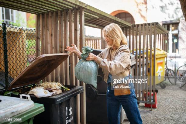 elderly woman throwing garbage in compost bin - throwing stock pictures, royalty-free photos & images