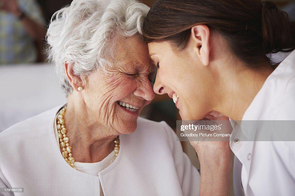 Ältere Frau berühren Gesicht der jungen weiblichen Krankenschwester : Stock-Foto