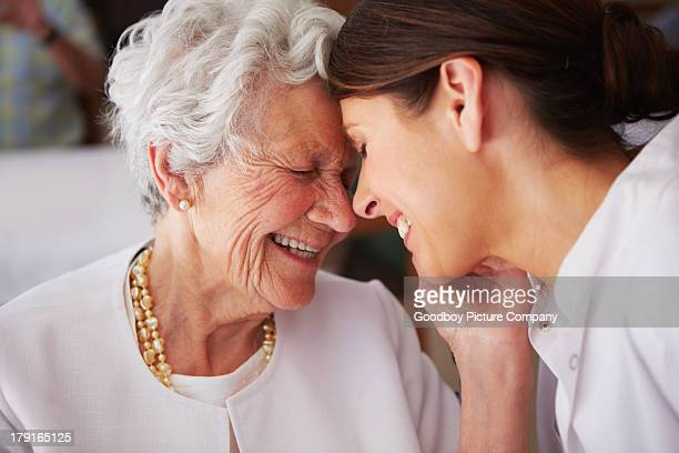 elderly woman touching face of young female nurse - seniore vrouwen stockfoto's en -beelden
