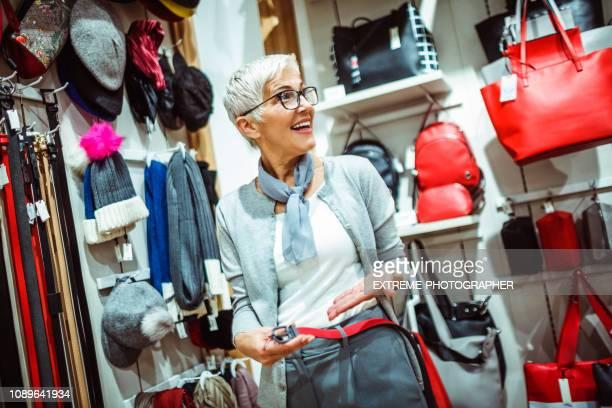 femme âgée essayer sur une ceinture en cuir rouge dans un magasin de sacs et accessoires - ceinture accessoire photos et images de collection