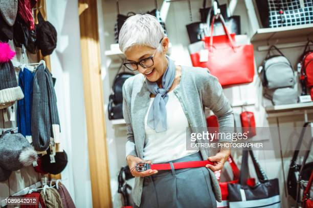 elderly woman trying on a red leather belt in a bags and accessories store - belt stock pictures, royalty-free photos & images