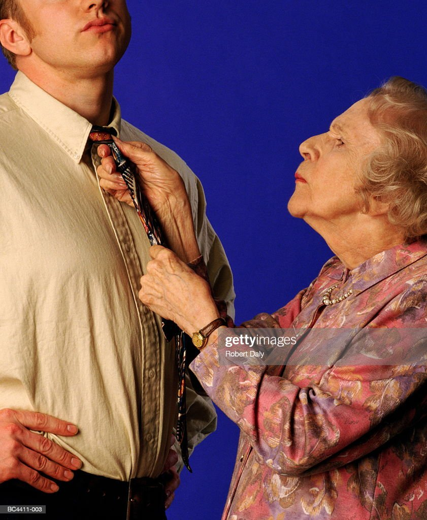 Elderly woman tying young man's tie, close-up : Stock Photo