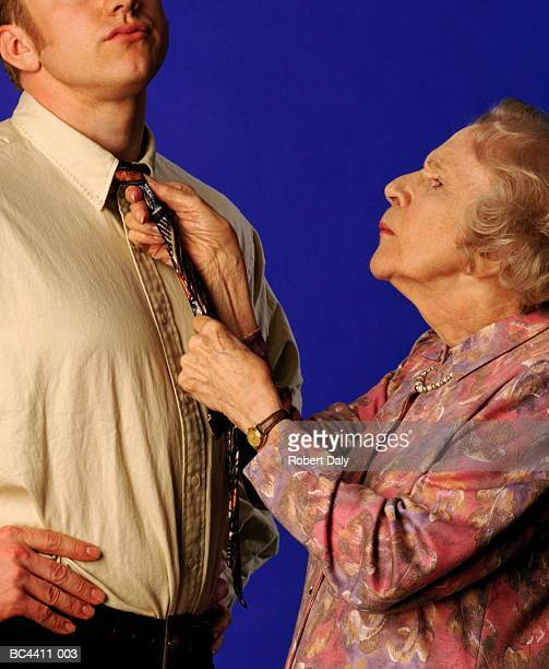 elderly woman tying young man's tie, close-up - mother in law stock pictures, royalty-free photos & images