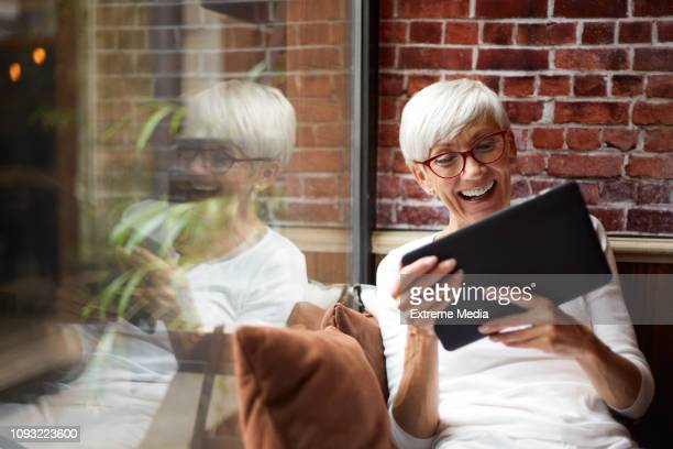 elderly woman using a digital tablet and having a good time while sitting comfortably next to a glass window - facetime stock pictures, royalty-free photos & images