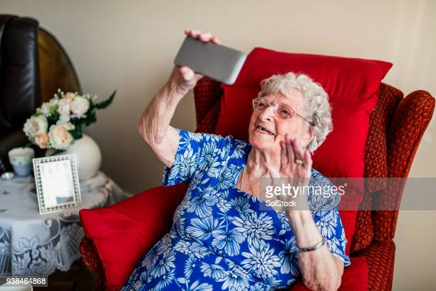 elderly woman using a mobile telephone - senior women stock pictures, royalty-free photos & images