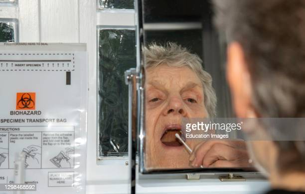 Elderly woman using a swab from the Coronavirus Home Test Kit about to take the nasal and throat swab test whilst looking in a mirror, England, UK.