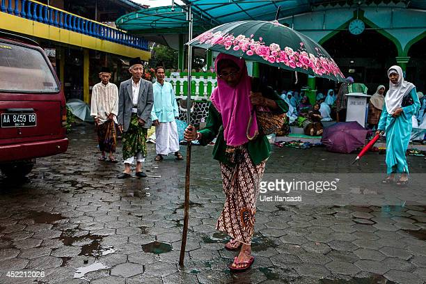A elderly woman using an umbrella as rain falls attends a boarding school Sepuh Payaman that cares for the elderly during Ramadan on July 15 2014 in...