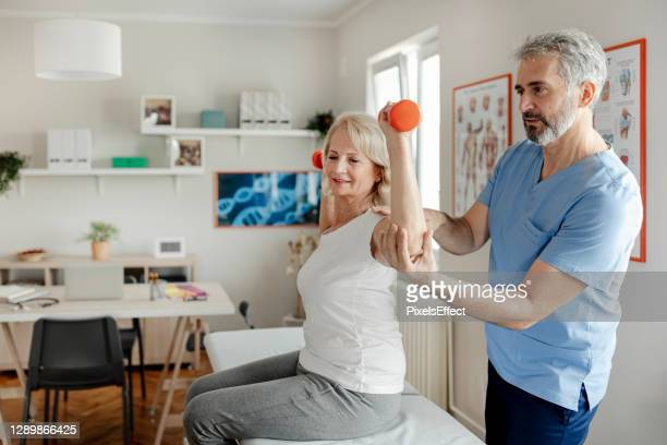 elderly woman using dumbbells with the help of a physical therapist - osteoporosis stock pictures, royalty-free photos & images