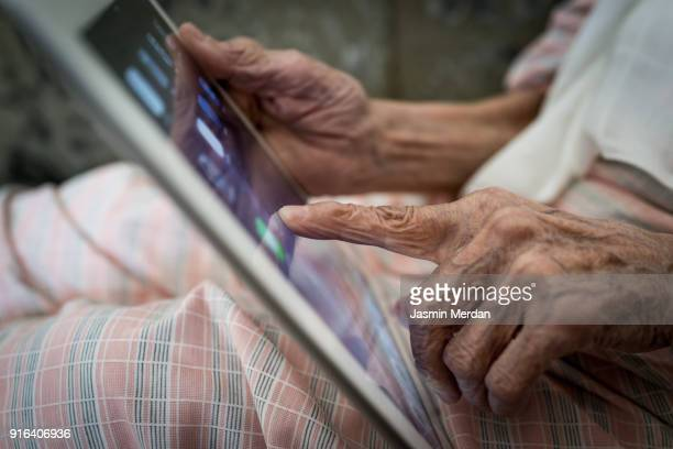 Elderly woman using tablet at home
