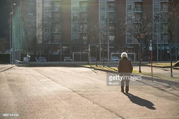 Elderly woman walking alone