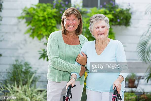 elderly woman walking with adult daughter - fragility stock pictures, royalty-free photos & images