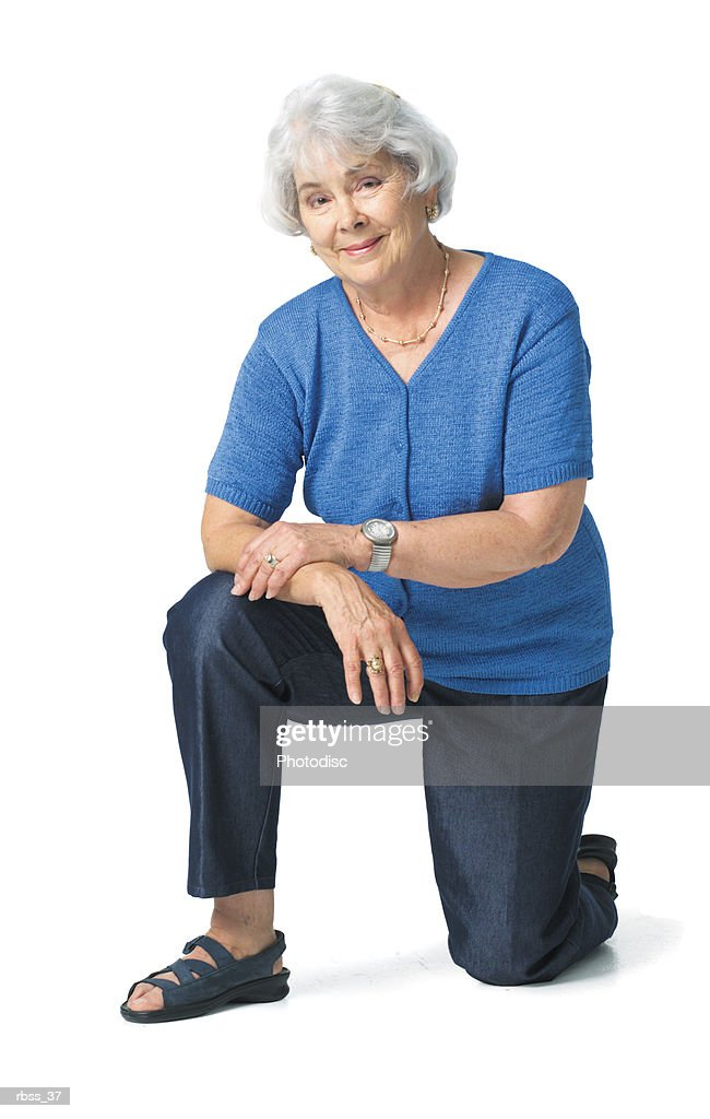 Elderly woman wearing a blue shirt kneels with one knee on the ground. : Foto de stock