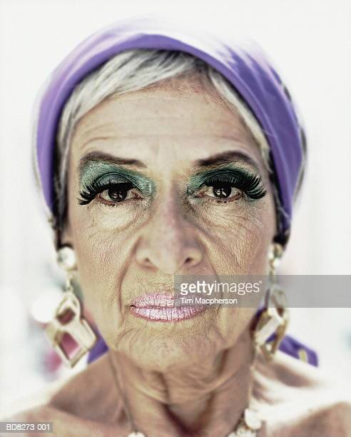 elderly woman wearing make-up and gold earrings, close-up, portrait - old ugly woman stock photos and pictures