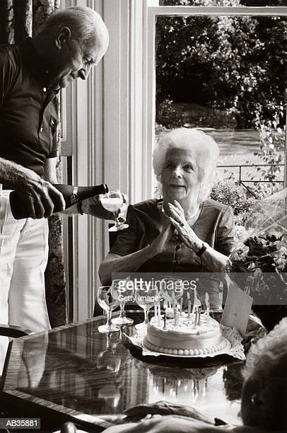 Elderly woman with birthday cake at party with friends, (B&W)