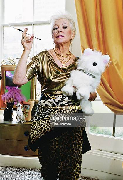 Elderly woman with cigarette holder and toy dog, portrait