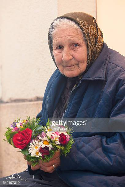 elderly woman with flowers - transylvania stock pictures, royalty-free photos & images