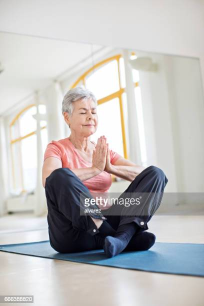 Elderly woman with hands clasped doing yoga in gym