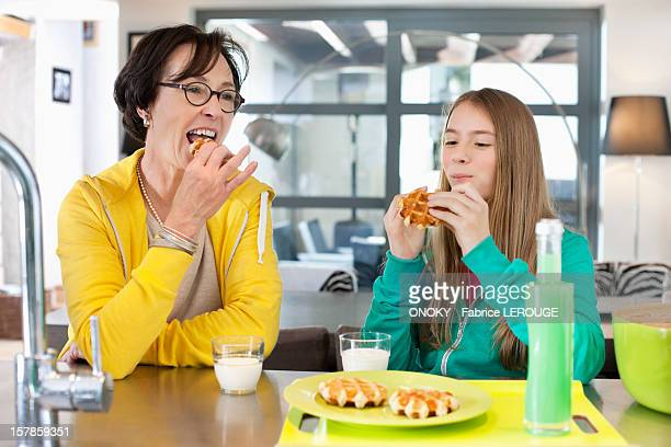 Elderly woman with her granddaughter eating waffles