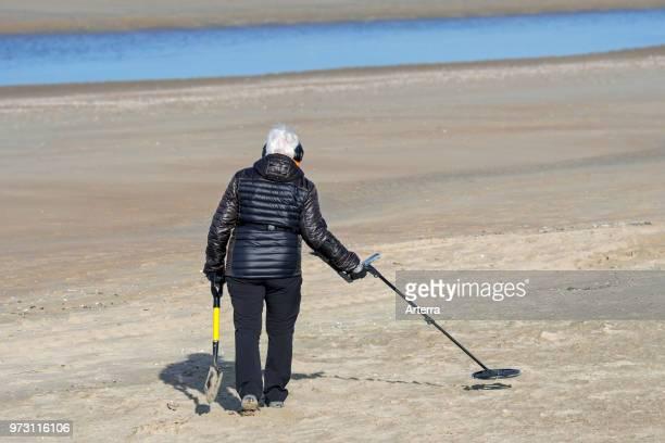 Elderly woman with metal detector beachcombing on sandy beach along the North Sea coast in winter