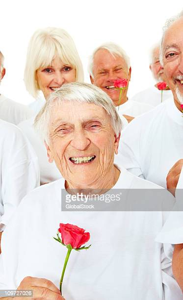 Elderly woman with rose smiling on white