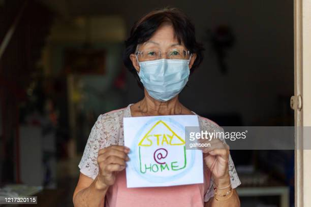 elderly woman with stay home drawing. pandemic concept - one senior woman only stock pictures, royalty-free photos & images