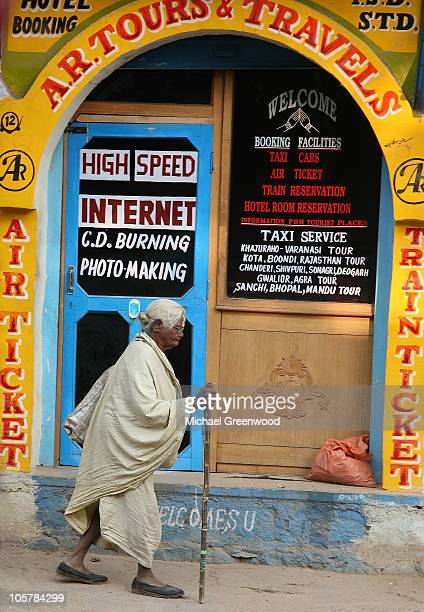 A elderly woman with walking stick and wearing a simple cloth passes an Internet Cafe in Orchha India Highlights the contrast between modern high...