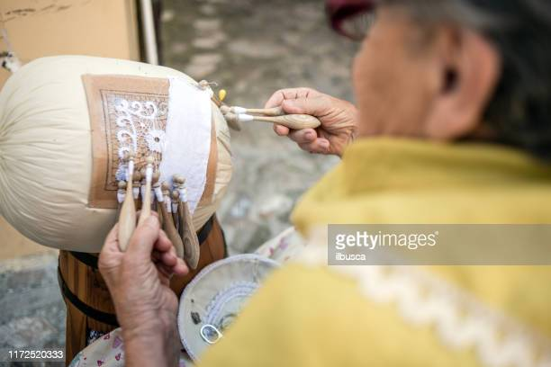 "elderly woman working on a ""merletto a tombolo"" (bobbin lace) in the street in front of her house in offida - lacemaking stock pictures, royalty-free photos & images"