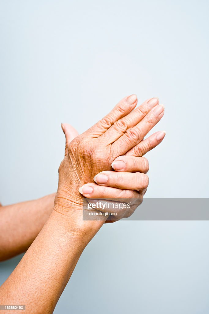 Elderly woman's with arthritis in her hands : Stock Photo