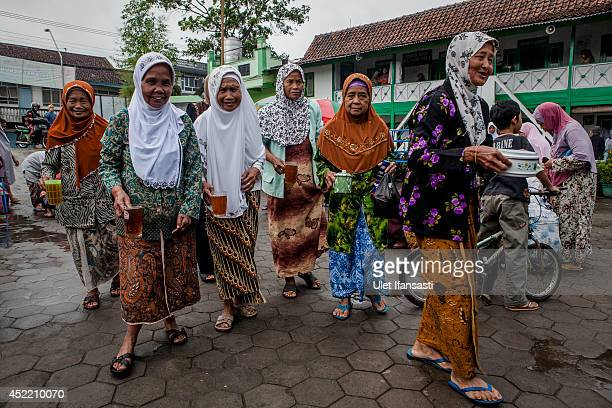 Elderly women carries a cup of tea and food as they prepare for a fasting break at a boarding school Sepuh Payaman that cares for the elderly during...