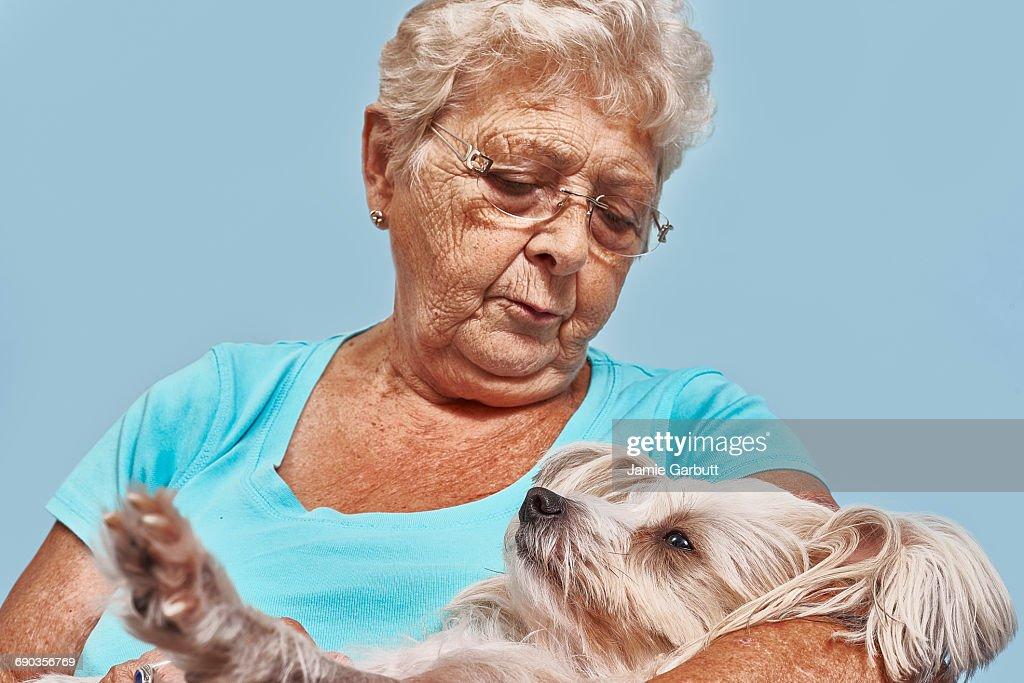 A elderly women cuddling her small dog. : Stock Photo