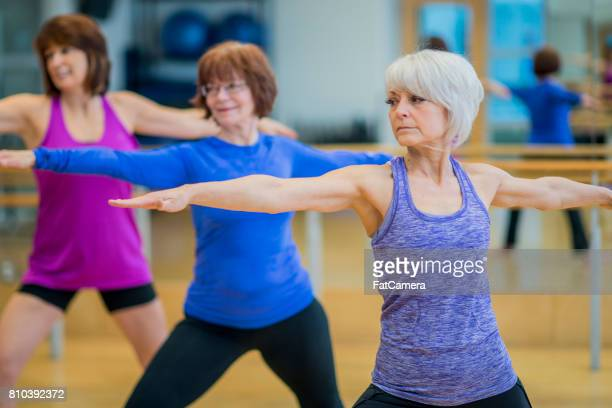 elderly women doing yoga together - yoga pants stock photos and pictures
