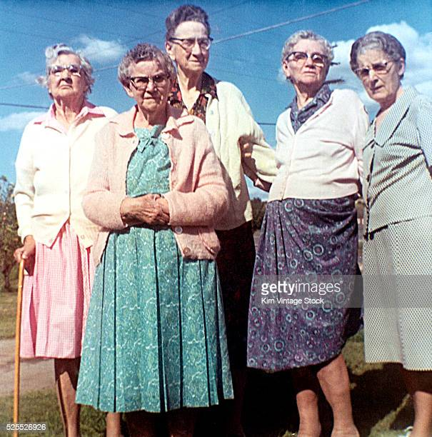 Elderly women pose for a group shot against a blue sky