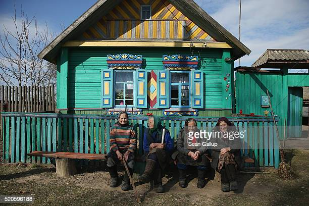 Elderly women sit next to a traditional house in the village of Pokats on April 4 2016 near Chachersk Belarus Chachersk and Pokats both located in...