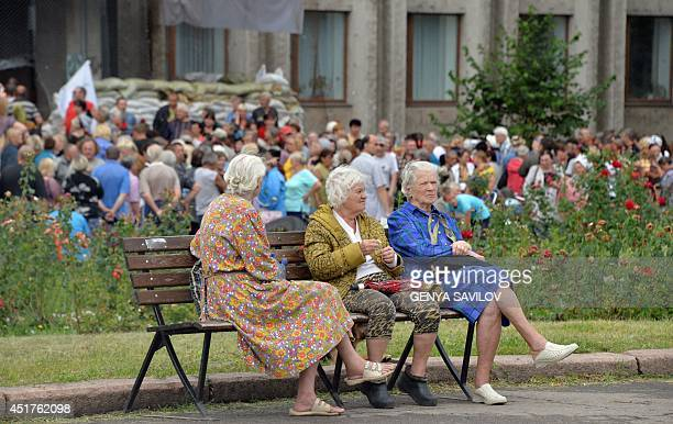 Elderly women sit on a bench as residents of the eastern Ukrainian city of Slavyansk queue outside the city hall on July 6, 2014 to receive...