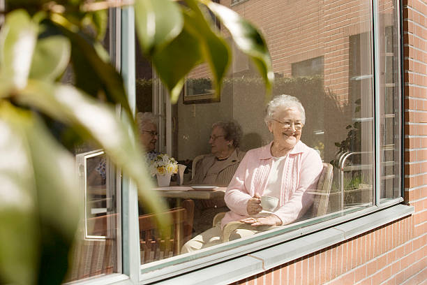 elderly women sitting in nursing home window - care home stock pictures, royalty-free photos & images