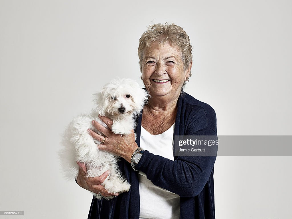 Elderly women smiling holding her puppy : Stock Photo