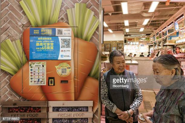 Elderly women stand next to a screen displaying an advertisement for Ant Financial Services Group's Alipay an affiliate of Alibaba Group Holding Ltd...